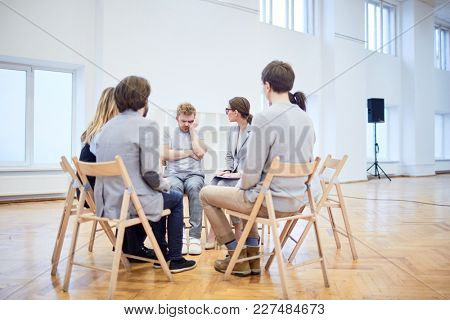 Group of young people with problems sitting in circle on chairs and looking at apathetic man during psychological session