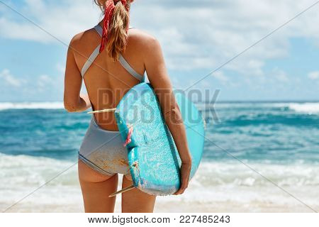 Back View Of Slim Young Female Model In Blue Swimsuit, Being Bored To Bathe At Beach, Carries Paddle