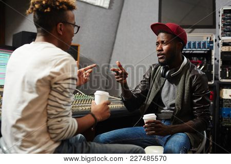 Young rapper explaining deejay which type of sound recording he wants to be produced