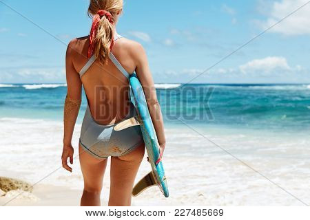 Cropped View Of Slim Female Model Fond Of Surfing, Stands Back To Ocean With Surf Board, Admires Blu