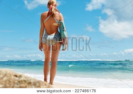 Full Length Portrait Of Unrecognizable Blonde Woman In Swimsuit, Stand Near Ocean With Surf Board, L