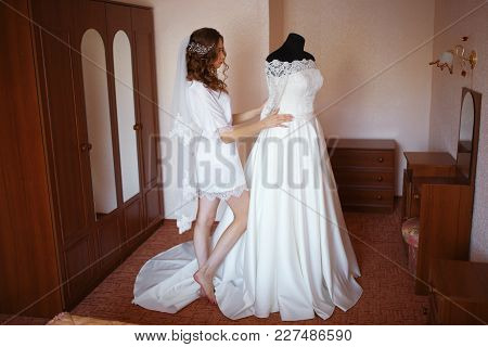 Beautiful Bride Girl With Makeup And Hairdo In White Dressing Gown In Bedroom