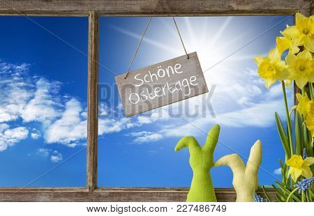 Sign With German Text Schoene Ostertage Means Happy Easter. Window Frame With View To Beautiful Sunn
