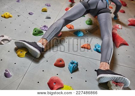 Legs of young climber in leggins and sports-shoes moving upwards along climbing wall