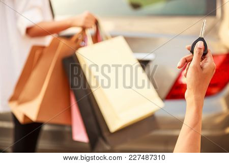 Female Ladies Carrying Colorful Shopping Bags In The Parking Lots Concept. Lady Hand Using Remote Co