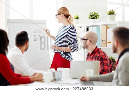 Business lady or teacher standing by whiteboard and pointing at financial document while group of people listening to her presentation