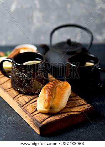 Cup of hot black tea with slice of lemon, honey and spices. Hot drink for a cold season