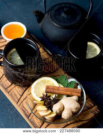 Cup of hot black tea with slice of lemon, honey and spices. Hot drink for a cold season, top view