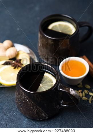 Two big ceramic cups of hot tea with lemon and spices. Hot drink for a cold season.