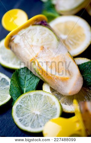 Healthy homemade lime and lavender popsicles with fresh mint leaves on a dark background