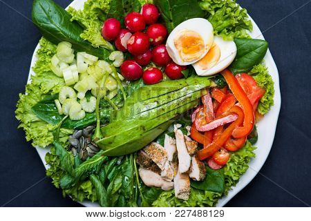 Fresh healthy salad with spinach, green leaf salad, celery, radish, bell pepper, avocado, chicken breast, pumpkin seeds and boiled egg. Healthy eating concept