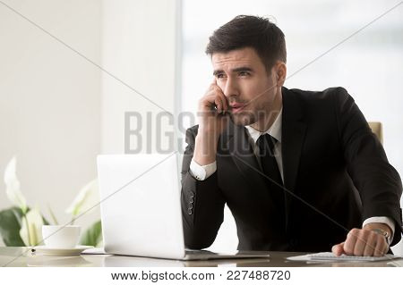 Portrait Of Successful Businessman In Black Business Suit Sitting At Desk With Laptop And Making Cal