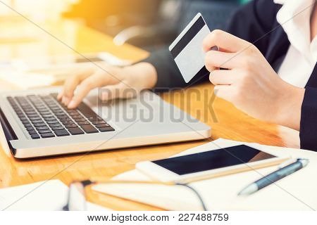 Business Woman Holding Credit Card And Using Computer To Make Her Online Purchase Or Banking Transca