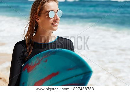 Close Up Shot Of Beautiful Young Blonde Female In Shades Spends Free Time At Popular Surf Location D