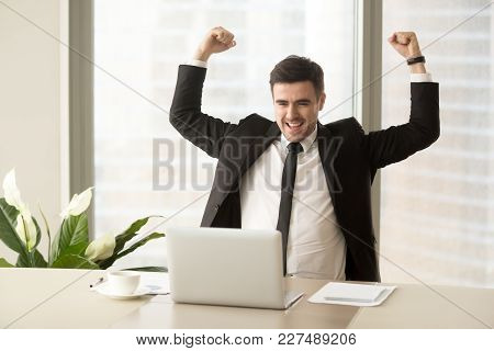 Millennial Businessman Raising Hands And Happily Yelling When Looking On Laptop At Desk. Business Le