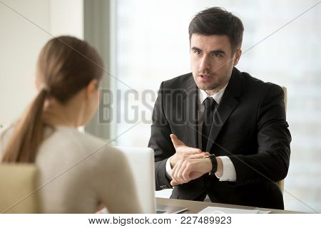 Angry Company Head Pointing At Watch Scolding Female Employee For Being Late At Work, Hurrying Manag