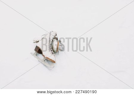 A Pair Of White Retro Ice Skates On The Snow. A Pair Of Ice Skates Lying On Snowy Background.