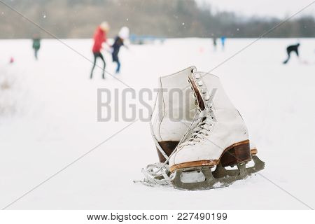 A Pair Of Female Ice Skates Lying On The Snow With Skaters In The Background. A Pair Of White Retro