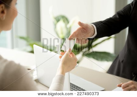 Company Male Manager Giving Blank Business Card Over Work Desk With Laptop To Female Client Or Busin