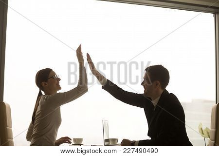 Happy Smiling Female And Male Business Partners Giving High Five While Sitting At Desk In Office. Bu