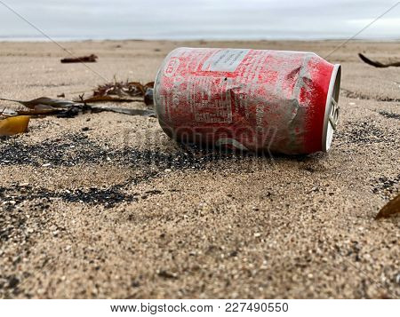 TROON, SCOTLAND - FEBRUARY 19, 2018: A weathered aluminium Coca Cola van washed up with seaweed on the beach at Troon near Glasgow, Scotland, UK.
