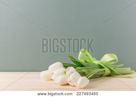 Beautiful Fresh Tulips In Bunch Bonded With Green Ribbon And Lying On Wood.