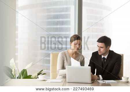 Millennial Businesswoman Discussing Company Indicators With Male Business Partner At Meeting In Offi