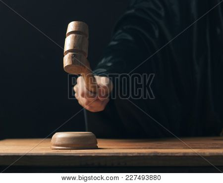 Hand Banging Gavel On Dark Background, The Judge Makes A Verdict, The Concept Of The Profession Of J
