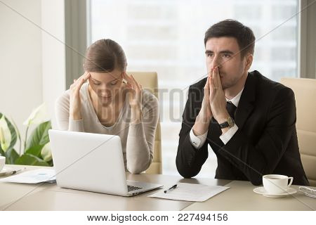 Tired Stressed Businessman And Businesswoman Sitting At Desk And Pondering Over Problem. Difficult N