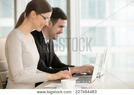 Smiling Young Woman In Eyeglasses And Positive Man In Business Suit Using Laptop While Sitting At De