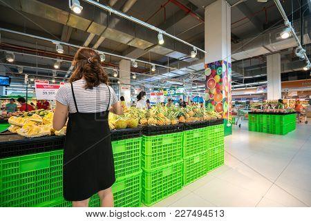 Hanoi, Vietnam - July 10, 2017: Asian Woman Buying Fresh Fruit At The Supermarket In Vinmart Superma