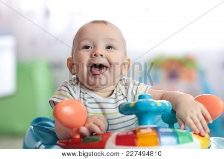 Portrait Of Funny Baby Boy At Steering Wheel Toy