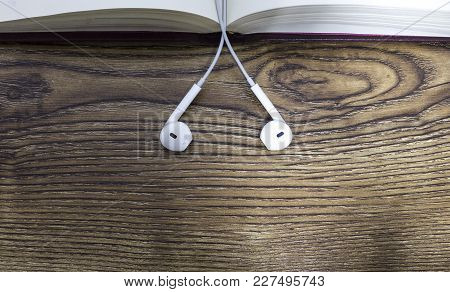 Book And Ear Plugs On Wooden Table.