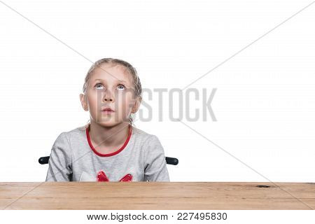 Thoughtful Girl Sits On A Chair At The Table And Looking Up, Isolated On A White Background