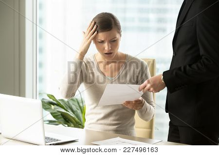 Boss Giving Dismissal Notification To Confused Female Office Worker. Millennial Woman Shocked Becaus
