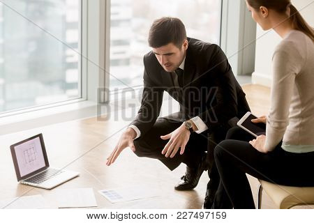 Male Real Estate Expert Explaining Benefits Of House For Potential Female Buyer When Showing Drawing