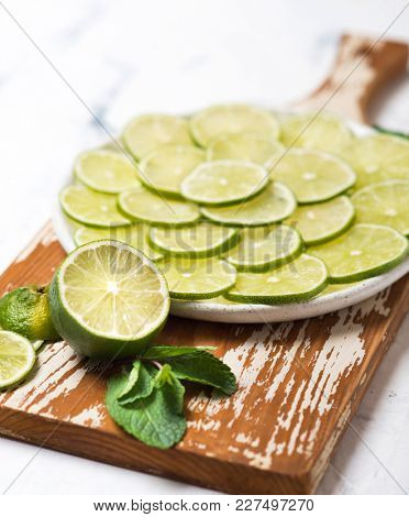 Citrus fruits. Fresh sliced limes and mint on the ceramic plate