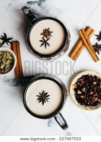Two big ceramic cups of hot tea with milk and spices. Hot drink for a cold season, top view