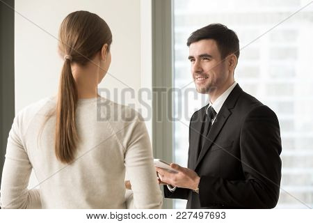 Portrait Of Smiling Millennial Businessman With Digital Tablet In Hands Looking At Female Coworker S