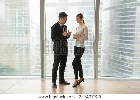 Female And Male Colleagues Discussing Work While Standing Near Large Window With Skyscrapers View Ou