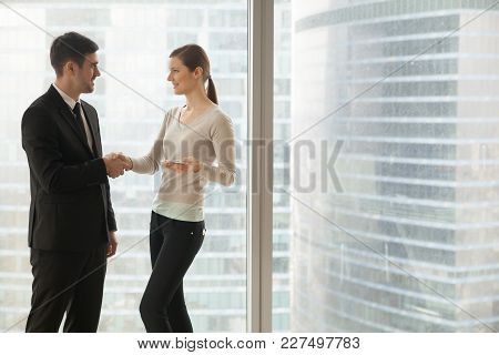 Smiling Female Secretary Welcoming Male Client In Company Office. Confident Businesswoman Introducin