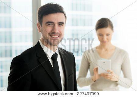 Portrait Of Handsome Smiling Millennial Businessman In Black Suit Standing In Office, Female Secreta