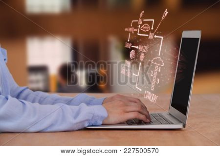 Cropped image of businesswoman using laptop against graphic designer using graphics tablet