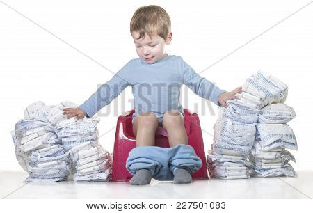 Happy Baby Boy Sitting On Chamber Pot Tearing Down Diaper Piles. Potty Training Concept