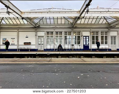 TROON, SCOTLAND - FEBRUARY 19, 2018: Passengers waiting for the train at Troon Station in Troon, South Ayrshire, Scotland, UK.
