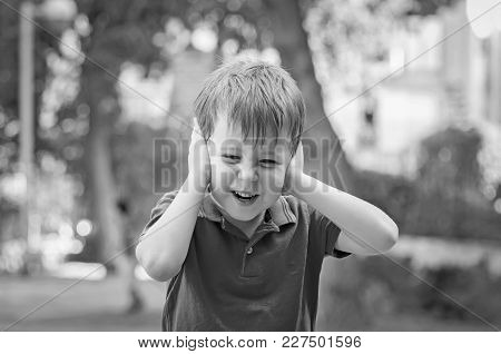 Stressed Out Little 5-year Old Caucasian Little Boy Outside Closing His Ears And Screaming Of Pain,