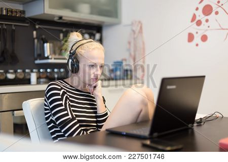 Woman In Her Casual Home Clothing Working And Studying Remotely From Her Small Flat Late At Night. H