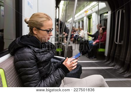 Young Girl Reading From Mobile Phone Screen While Traveling On Metro. Wireless Internet On Public Tr