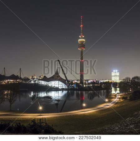 The Skyline Of Munich In Bavaria, Germany, With Reflections In The Lake And Stars In The Sky During