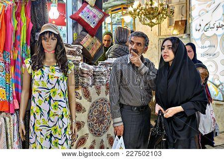 Tehran, Iran - April 29, 2017: A Young Woman In Black Islamic Hijab, Talking To A Mature Man, Standi